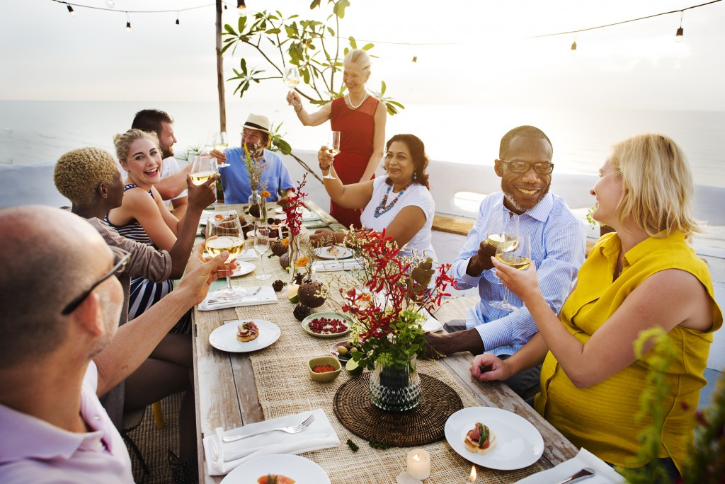 People gather around outdoor dinning table for a toast