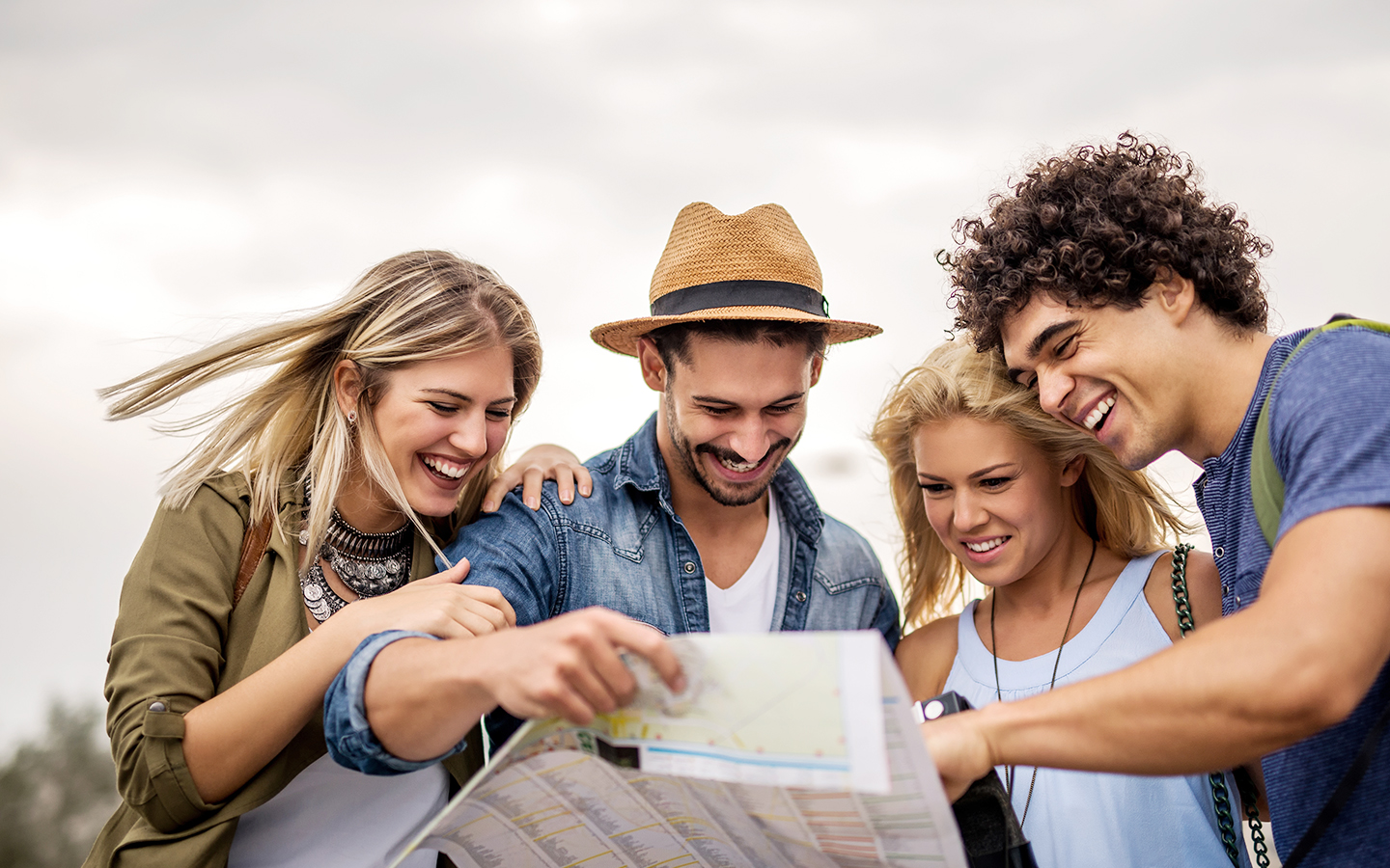 Traveling friends examine a map and smile