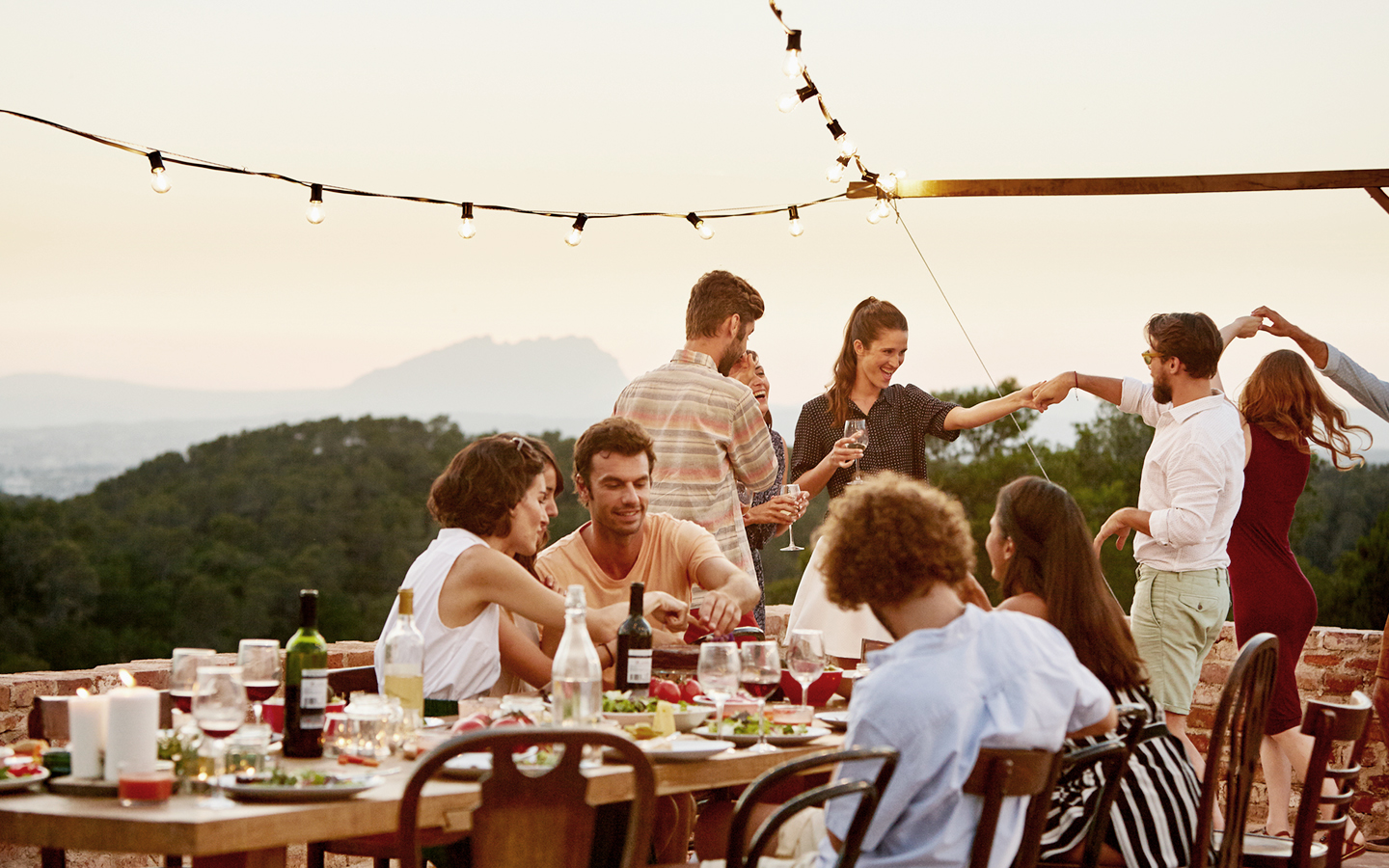 Friends dance and gather around table to eat